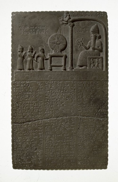 Illustration: Tablet sculptured with a scene representing the worship of the Sun-god in the Temple of Sippar.  The Sun-god is seated on a throne within a pavilion holding in one hand a disk and bar which may symbolize eternity.  Above his head are the three symbols of the Moon, the Sun, and the planet Venus.  On a stand in front of the pavilion rests the disk of the Sun, which is held in position by ropes grasped in the hands of two divine beings who are supported by the roof of the pavilion.  The pavilion of the Sun-god stands on the Celestial Ocean, and the four small disks indicate either the four cardinal points or the tops of the pillars of the heavens.  The three figures in front of the disk represent the high priest of Shamash, the king (Nabu-aplu-iddina, about 870 B.C.) and an attendant goddess. [No. 91,000.]
