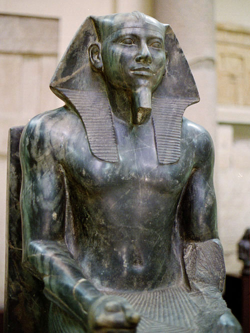 Statue of Khafre in diorite. Valley Temple of Khafra, Giza. Egyptian Museum, Cairo.  Main floor - room 42. Diorite: height 168 cm, width 57 cm, depth 96 cm. JE 10062 - CG 14. https://en.wikipedia.org/wiki/Khafra#/media/File:Khafre_statue.jpg Jon Bodsworth - http://www.egyptarchive.co.uk/html/cairo_museum_10.html