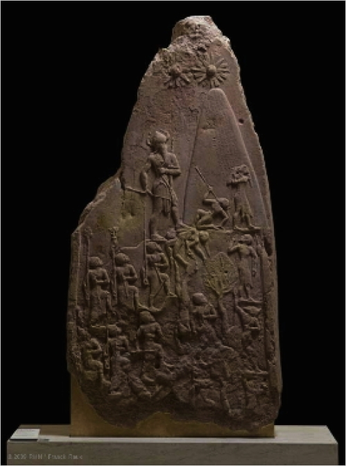 The brilliance of Naram-Sin's reign is reflected in the execution of this stele, which commemorated his victory over Satuni, king of the Lullubi.  The Akkadian army is climbing the steep slopes of the Zagros Mountains, home to the Lullubi. This upward march sweeps aside all resistance. To the right of a line of trees clinging to the mountainside, defeated enemies are depicted in a posture of submission. Those who have been killed are trampled underfoot by the Akkadian soldiers or drop over the precipice. These mountain people are clad in a tunic of hide and wear their long hair tied back. The composition is dominated by the lofty figure of the king, to whom all eyes - those of the Akkadian soldiers and of their Lullubi enemies - are turned. The triumphant sovereign, shown taller than the other men in the traditional manner, leads his army in the attack on the mountain.  He is followed by standard bearers who march before helmeted soldiers carrying bows and axes. Naram-Sin tramples the bodies of his enemies, while a kneeling Lullubi tries to tear out the arrow piercing his throat. Another raises his hands to his mouth, begging the Akkadian king for mercy.  But the conqueror's gaze is directed toward the top of the mountain. Above Naram-Sin, solar disks seem to radiate their divine protection toward him, while he rises to meet them. The Akkadian sovereign wears a conical helmet with horns - a symbol traditionally the privilege of the gods - and is armed with a large bow and an axe. This victorious ascension chiseled in stone thus celebrates a sovereign who considers himself on an equal footing with the gods. In official inscriptions, Naram-Sin's name was therefore preceded with a divine determinative.  He pushed back the frontiers of the empire farther than they had ever been, from Ebla in Syria to Susa in Elam, and led his army