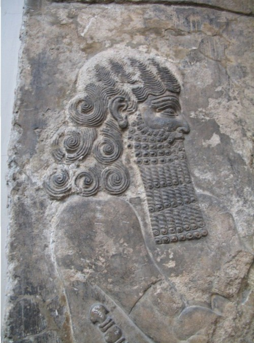 "Lahmu, ""Hairy,"" is a protective and beneficent deity, a first-born son of Apsu and Tiamat.  He and his sister Laḫamu are the parents of Anshar and Kishar, the sky father and earth mother, who birthed the gods of the Mesopotamian Pantheon. Laḫmu is depicted as a bearded man with a red sash--usually with three strands--and four to six curls on his head. He is often associated with the Kusarikku or ""Bull-Man."" In Sumerian times Laḫmu may have meant ""the muddy one"". Lahmu guarded the gates of the Abzu temple of Enki at Eridu. He and his sister Laḫamu are primordial deities in the Babylonian Epic of Creation-–Enuma Elis. http://foundfact.com/portfolio-view/lahmu/#!prettyPhoto http://foundfact.com/library/beings-people-and-gods/page/6/#!prettyPhoto"
