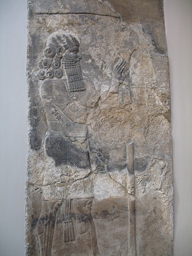 "Lahmu, ""Hairy,"" is a protective and beneficent deity, the first-born son of Apsu and Tiamat. He and his sister Laḫamu are the parents of Anshar and Kishar, the sky father and earth mother, who birthed the gods of the Mesopotamian Pantheon. Laḫmu is depicted as a bearded man with a red sash-usually with three strands- and four to six curls on his head. He is often associated with the Kusarikku or ""Bull-Man."" In Sumerian times Laḫmu may have meant ""the muddy one"". Lahmu guarded the gates of the Abzu temple of Enki at Eridu. He and his sister Laḫamu are primordial deities in the Babylonian Epic of Creation –Enuma Elis and Lahmu may be related to – or identical with- 'Lahamu' one of Tiamat's Creatures in that epic. http://foundfact.com/portfolio-view/lahmu/#!prettyPhoto http://foundfact.com/library/beings-people-and-gods/page/6/#!prettyPhoto"