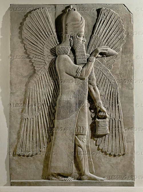 Now compare this Nimrud bas relief from the Louvre: an ummânū sprinkles water with a mullilu cone in his right hand, holding his banduddu bucket in his left. This ummânū wears bracelets with a concentric circular design, and rosettes are not apparent. This ummânū also wears the common horned headdress of Anu, but with three stacked layers of horns. As noted elsewhere, this headdress is surmounted by an object that resembles a partial fleur de lis. From Nimrud, capital of king Ashurnarzipal.  Louvre, AO 19845
