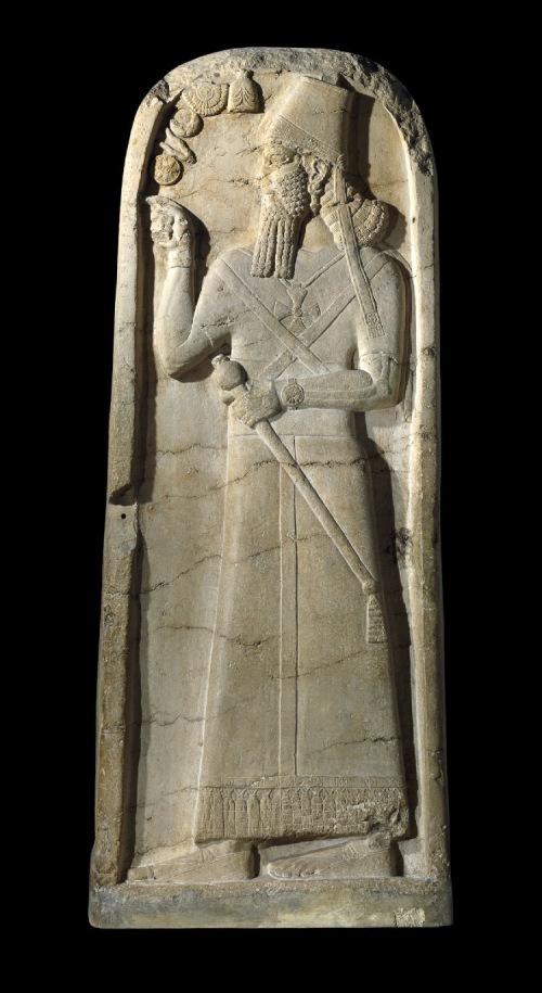 A stele of the Assyrian king Šamši-Adad V (c.815 BCE), standing in the gesture of blessing before five divine emblems:<br />  (1) the crown of the sky-god Anu, with three horns; <br />  (2) the winged disk, often associated with Marduk or Aššur; <br />  (3) the disk and crescent associated with the Moon god Sin; <br />  (4) the fork associated with Nabu (?); <br />  (5) the eight-pointed star of Ishtar.<br />  It is now apparent that the horned crown of Anu is portrayed on numerous depictions of ummanū, or human apkallū.<br />  The cross worn as an amulet is a symbol of the sun god, Šamaš.