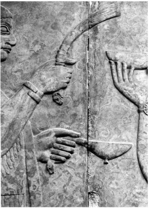 Detail on the whisk and the cup in the hands of a priest. This bas relief is singular in its fine detail and superb preservation. The individual strands of the fly whisk are readily apparent, as is the detail of the lion headed handle beneath the hand of a beardless priest. The fingernails are clearly visible.<br />  A snake-headed handle from what appears to be a ladle is apparent in the lower hand.<br />  From Panels 2-3, Room G, Northwest Palace of Ashurnasirpal II at Nimrud.<br />  London, British Museum ANE 124564-124565.<br />  Photo: Mehmet-Ali Atac, The Mythology of Kingship in Neo-Assyrian Art, 2010, p. 99.