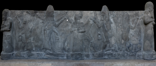 Click to zoom.<br /> A solid basalt tub recovered from outside the Temple of Ishtar at Nineveh, now in the collection of the Pergamon Museum.<br />  Ea is readily identified at the center with water flowing from his shoulders. Ea is surrounded by apkallu, puradu-fish apkallu.<br />  The puradu-fish apkallu have a fish head and fish skin flowing down their backs. They raise rectangular objects of unknown etiology in their right hands, in their traditional acts of purification and blessing. The banduddu buckets are, as usual, in their lowered left hands.<br />  This tub probably portrays the Seven Sages of antediluvian Sumeria.